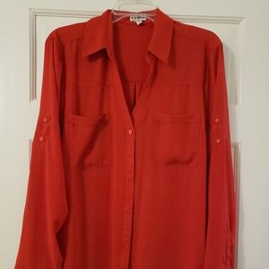 Red blouse, sleeves can be buttoned up.